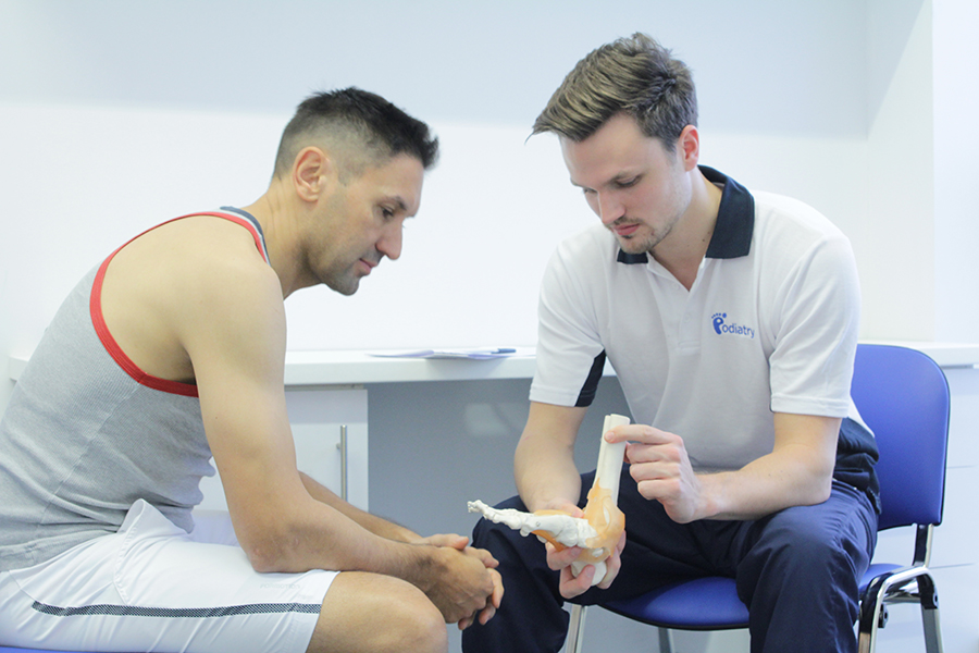 Specialist showing patient the mechanics of the foot.