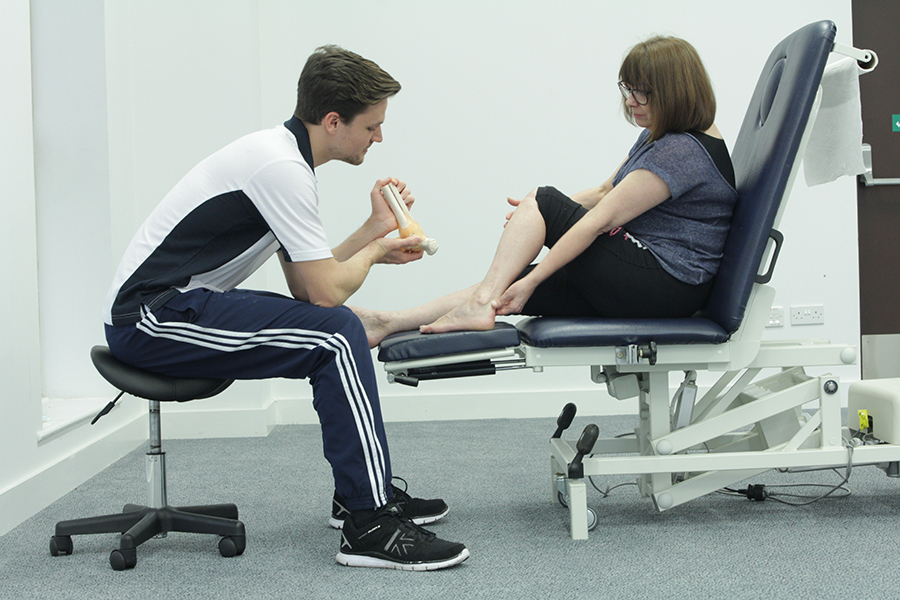 Specialist showing the mechanics of the foot to a patient.