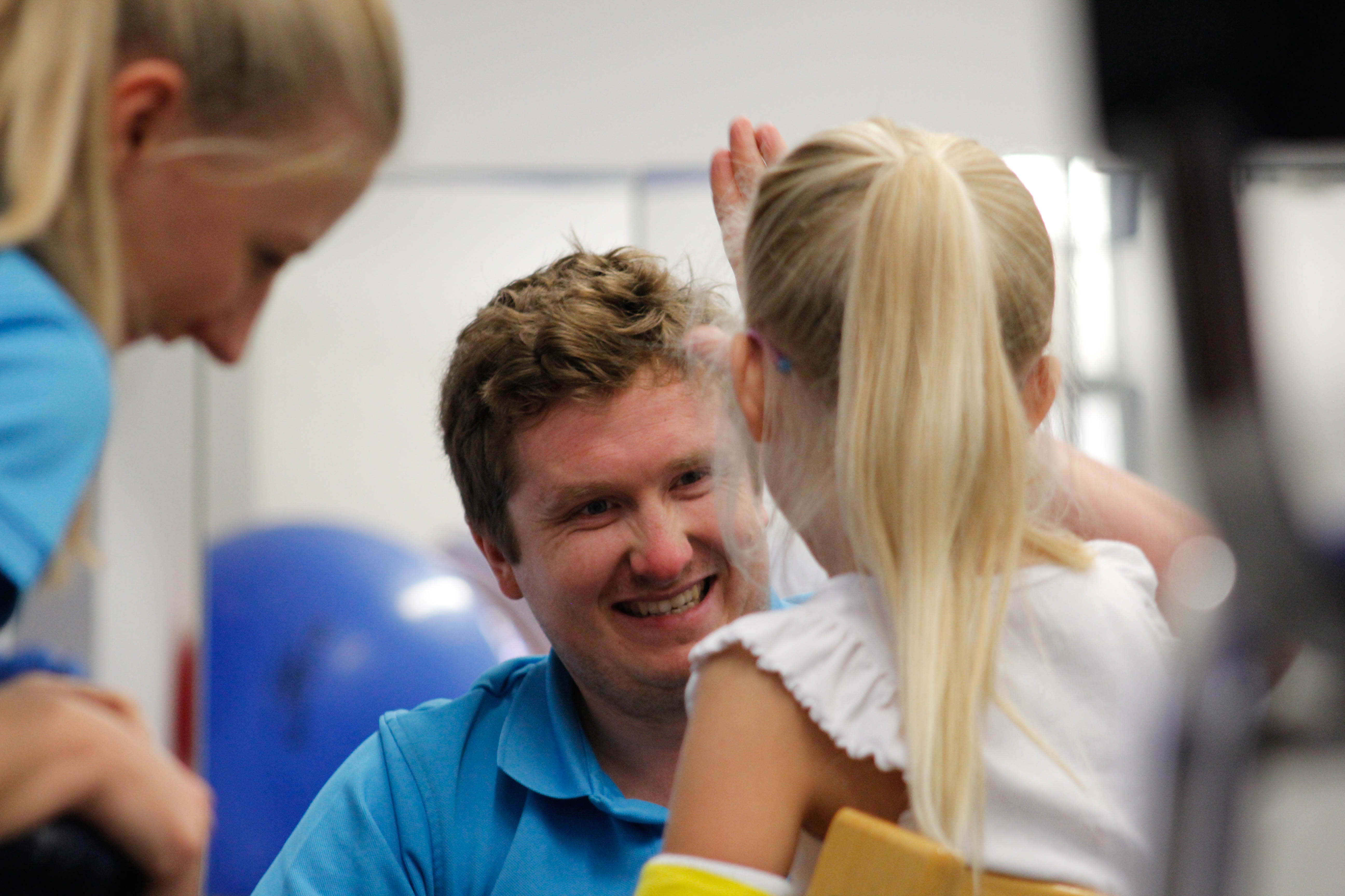 CIMT therapist smiling at small child.