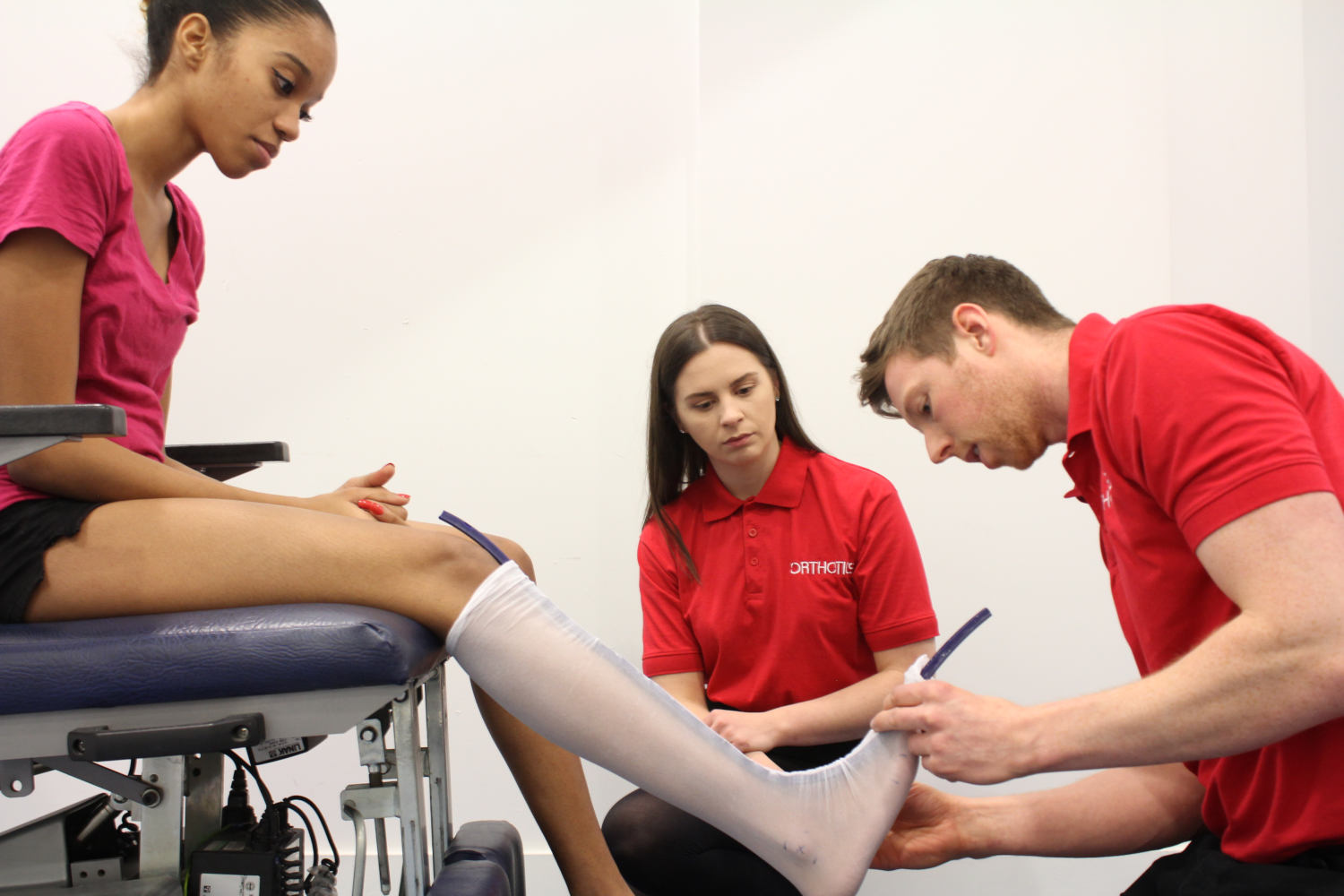 Pair of Orthotics professionals working with a young girl.