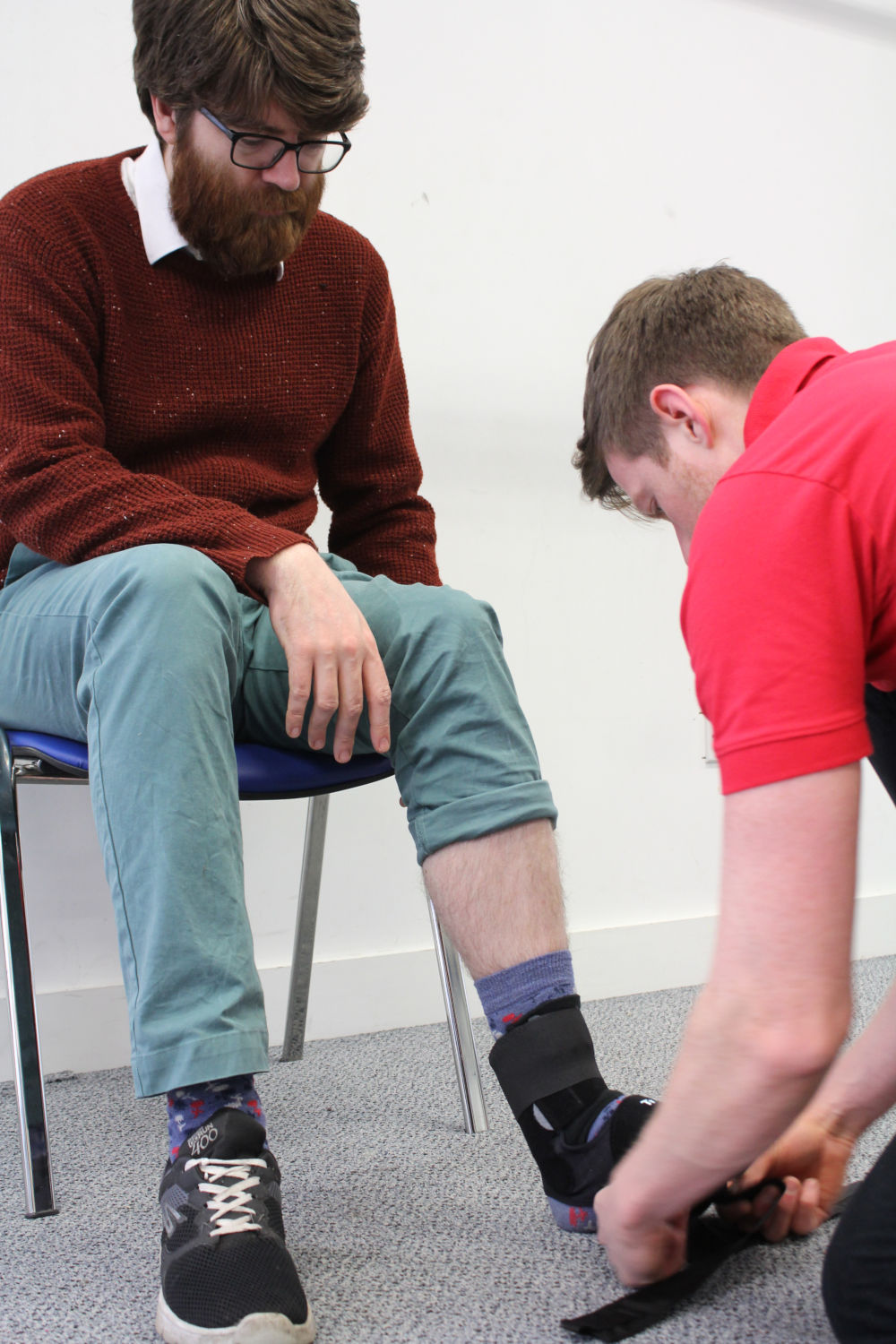 Man sat whilst Orthotics professional adjusts his angle support.