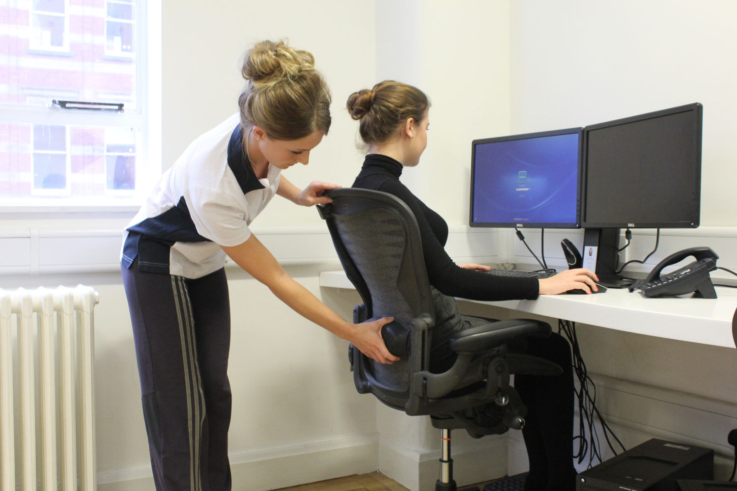 Admin staff member sat with good posture with support from Physio specialist.