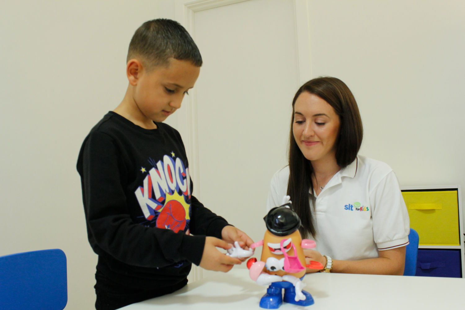 SLT for Kids therapist observing boy play with Mr. Potato Head.
